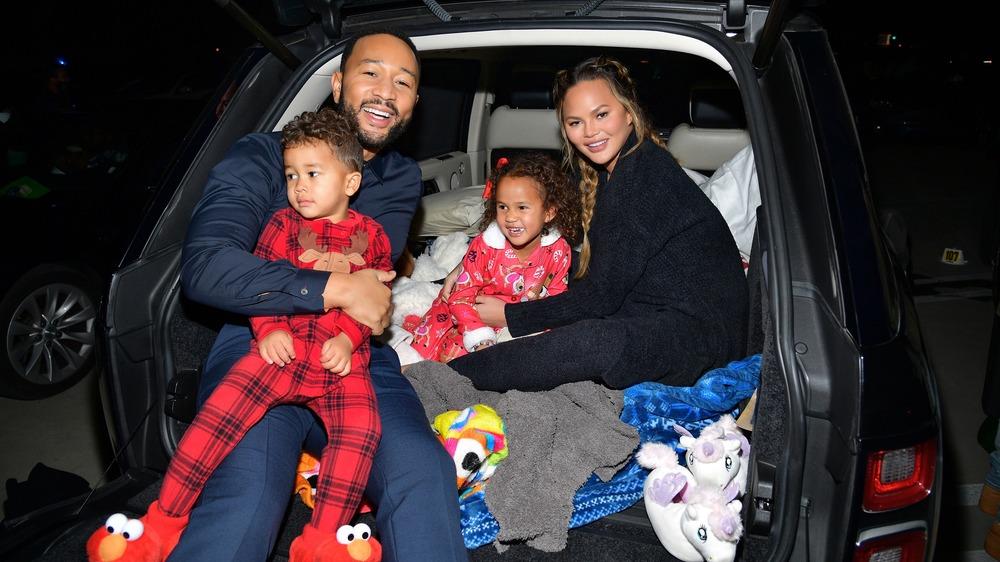 John Legend and Chrissy Teigen smiling with kids