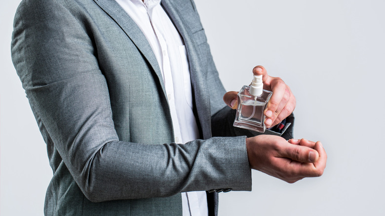 Man spraying perfume on wrist
