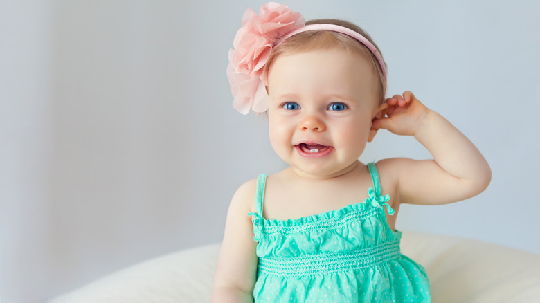 baby with ping flower in hair