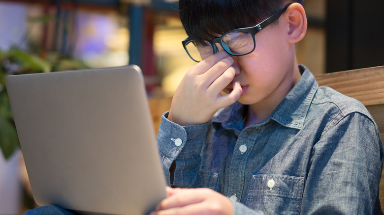 Boy looking at a screen with tired eyes
