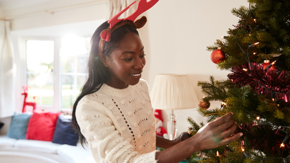 A woman decorates her Christmas tree, while wearing reindeer ears.