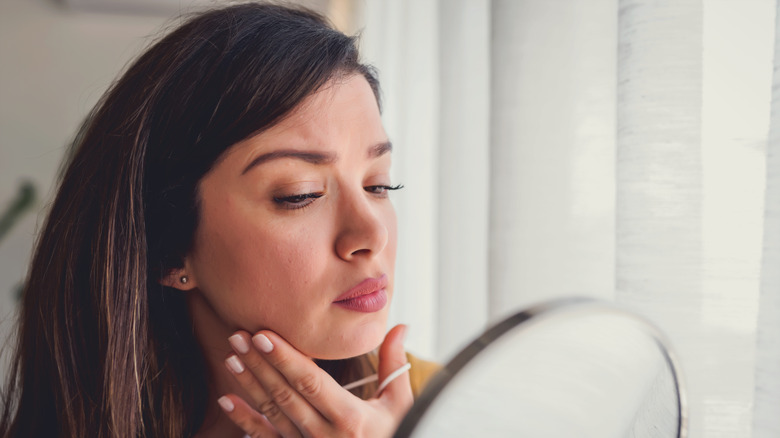 A woman inspecting her skin in a mirror