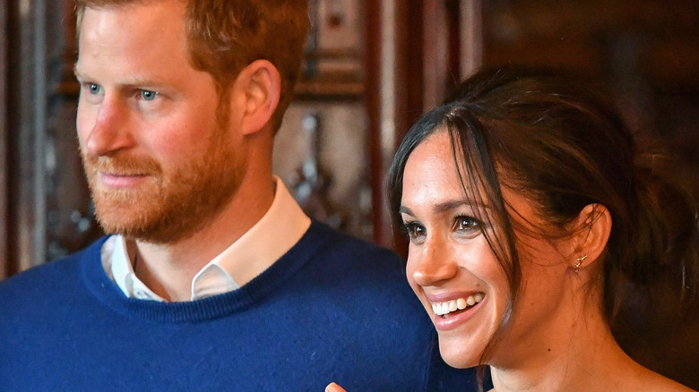 Prince Harry and Meghan Markle smile at an event.