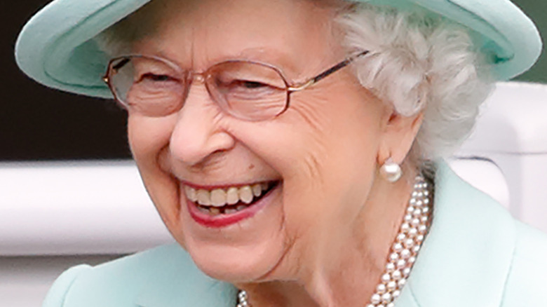 Queen Elizabeth II smiling and looking to the side in turquoise hat