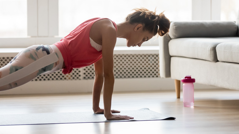 woman doing push-ups in her home