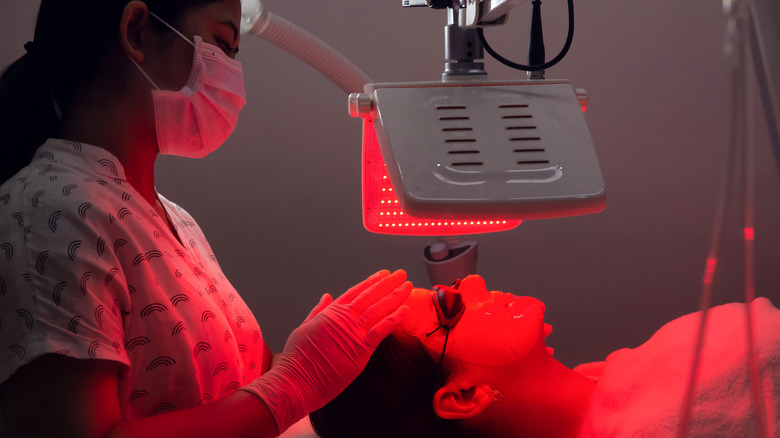 Woman receiving treatment with red light therapy