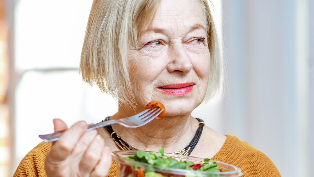 Older woman eating vegetables