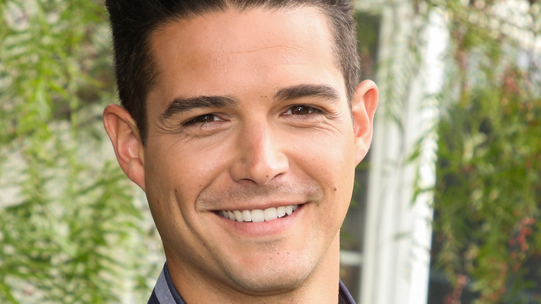 Wells Adams smiles in front of greenery backdrop