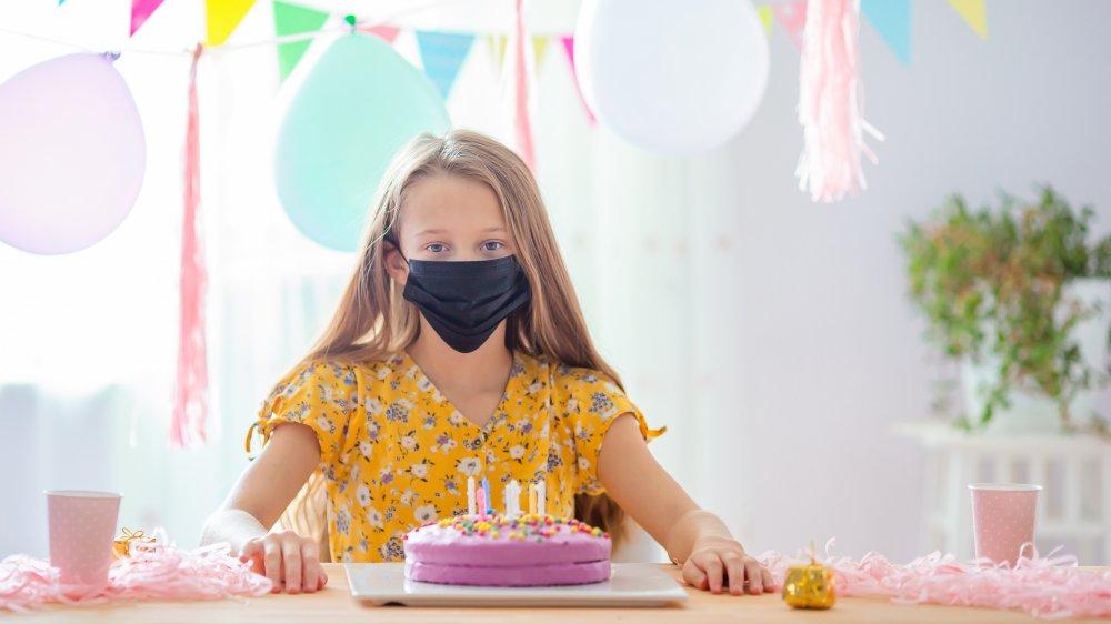 girl with mask and birthday cake