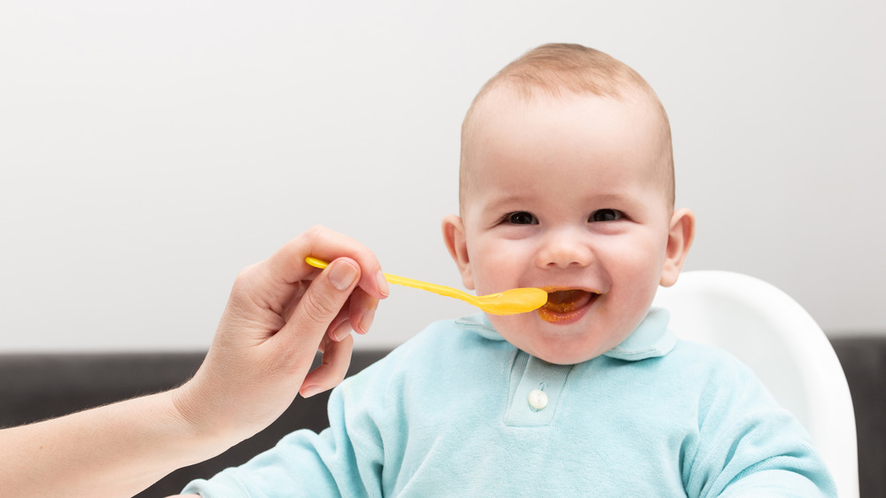 A hand feeding a baby a spoonful of food