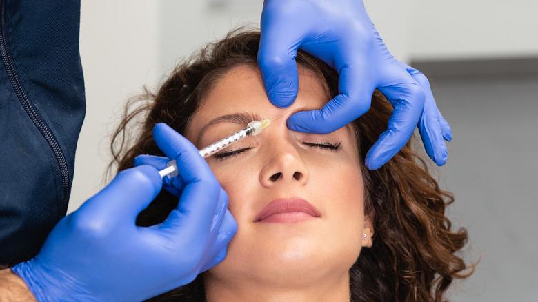 Woman receiving botox injection between eyebrows
