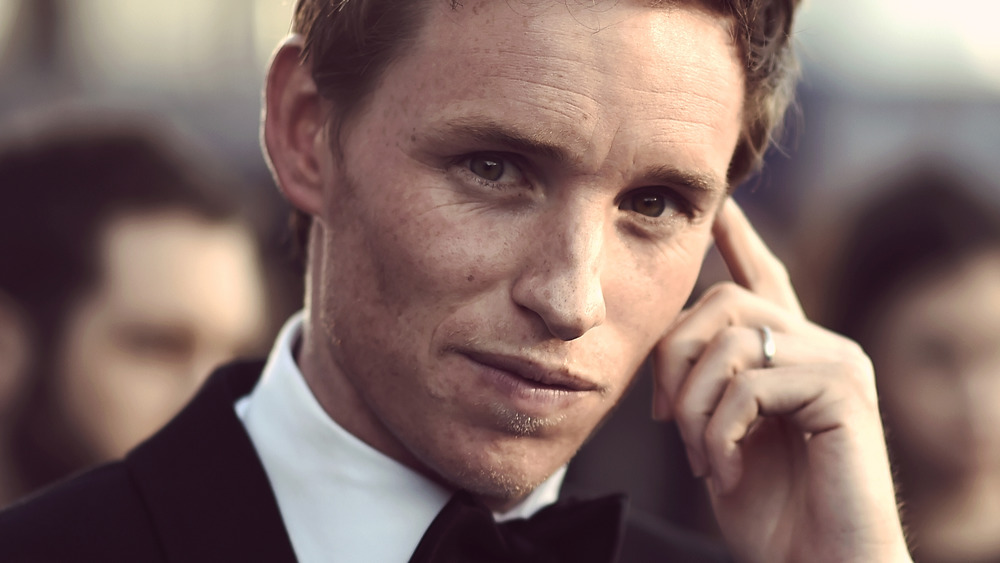 Eddie Redmayne holding a finger to his temple