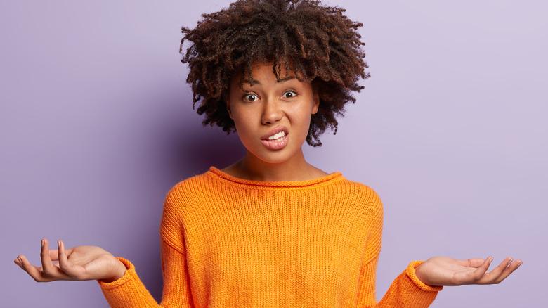 Woman wearing orange sweater shrugging her shoulders.