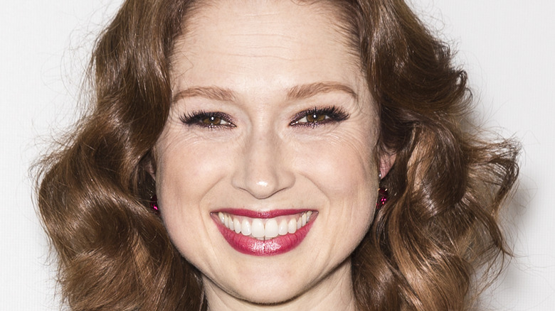 Ellie Kemper smiles with red lips and curly hair.
