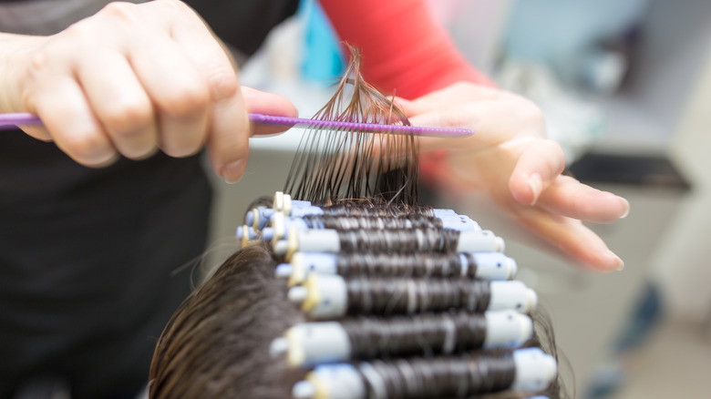 Hairstylist giving client a perm