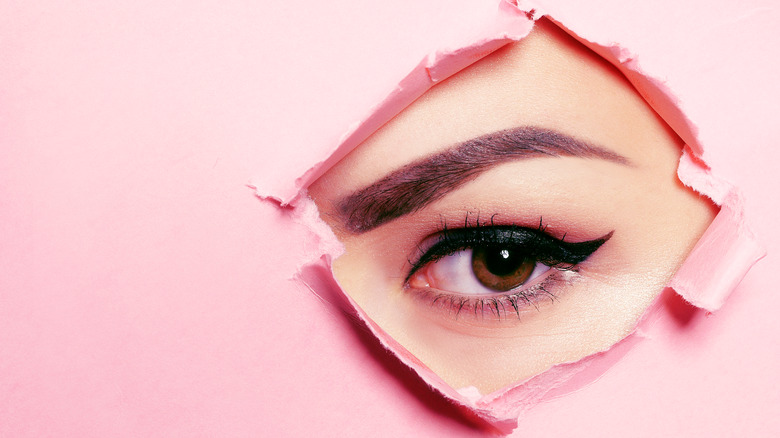 Woman's eye showing through a ripped pink paper
