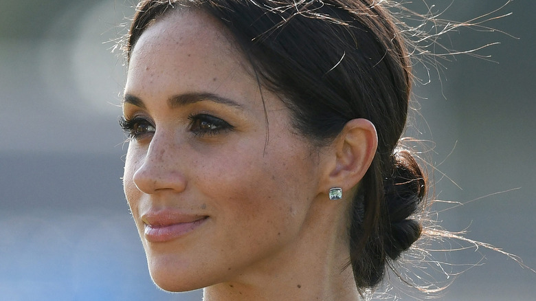 Meghan Markle smiling, side profile.