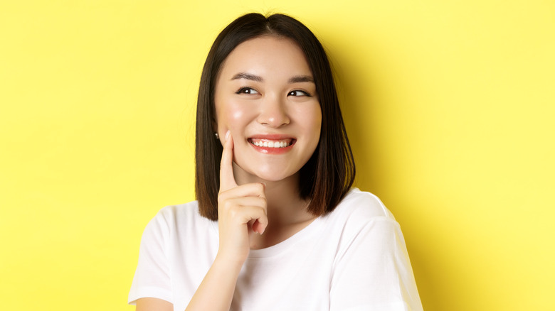 Young woman smiling, touching her cheek