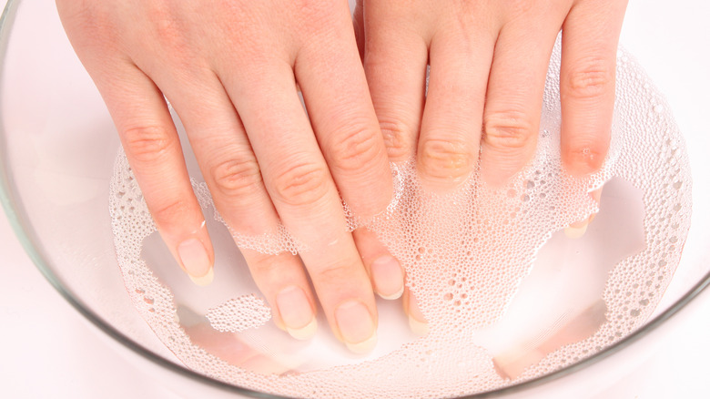 Close up of a woman's hands soaking in a clear bowl of soapy water.