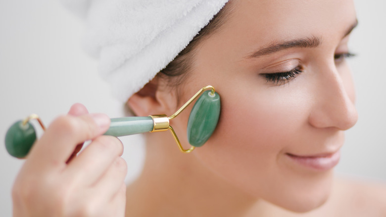 Woman using a jade roller on her face
