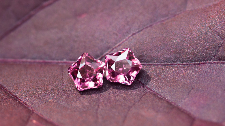 Two pink tourmaline gemstones on a pink leaf