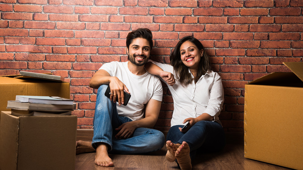 A couple sitting in front of an exposed brick wall among boxes