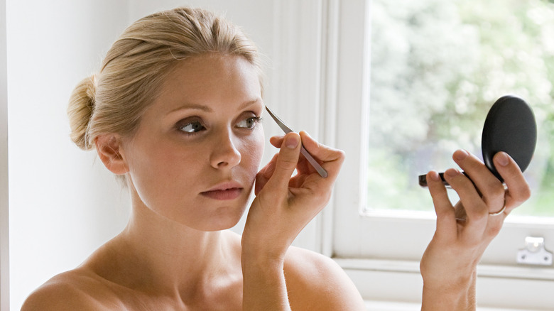 woman plucking eyebrows while looking in compact mirror