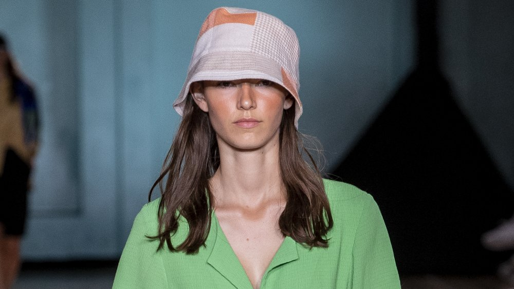 model wearing a patchwork bucket hat, two fashion trends that aren't worth the money