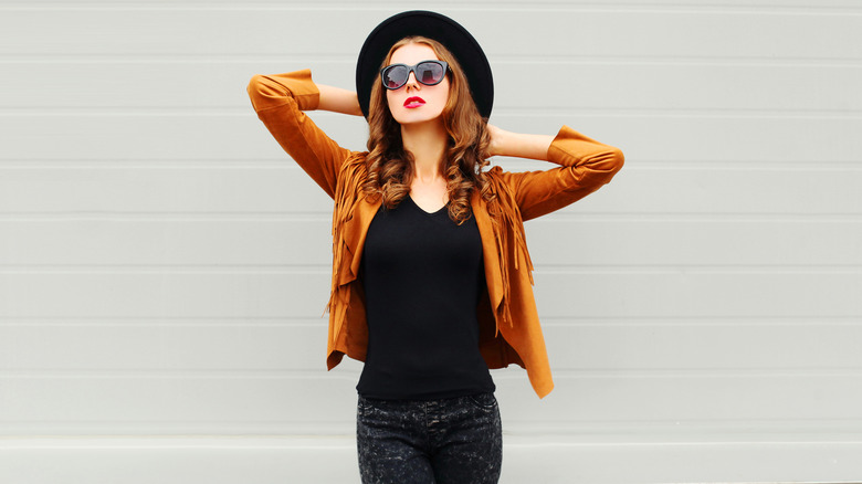 Fashion trends woman in leather fringe coat and big  sunglasses