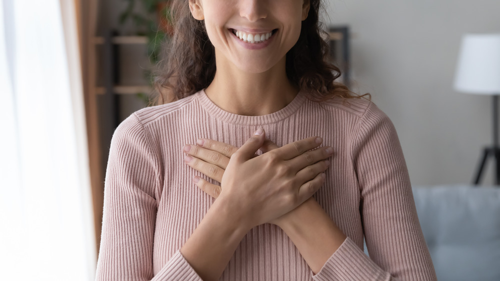 Woman clasping hands on chest