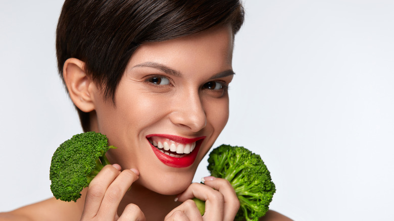 woman with broccoli and healthy skin