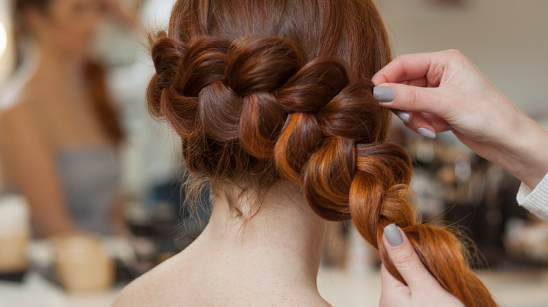 Woman wearing her red hair in a French braid