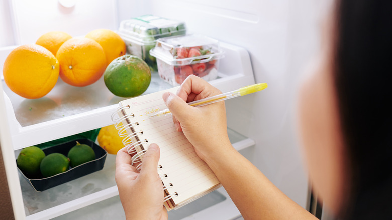 Woman checking her fridge and making a grocery list