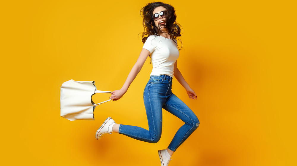 Woman with skinny jeans jumps in the air
