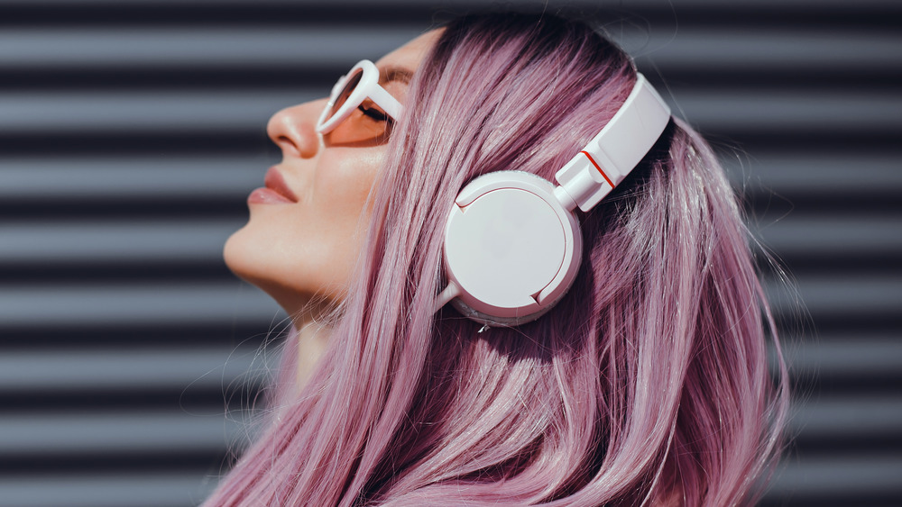 A woman with pink hair wearing headphones