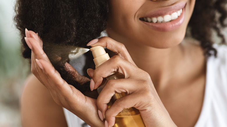 Woman applying hair spritz