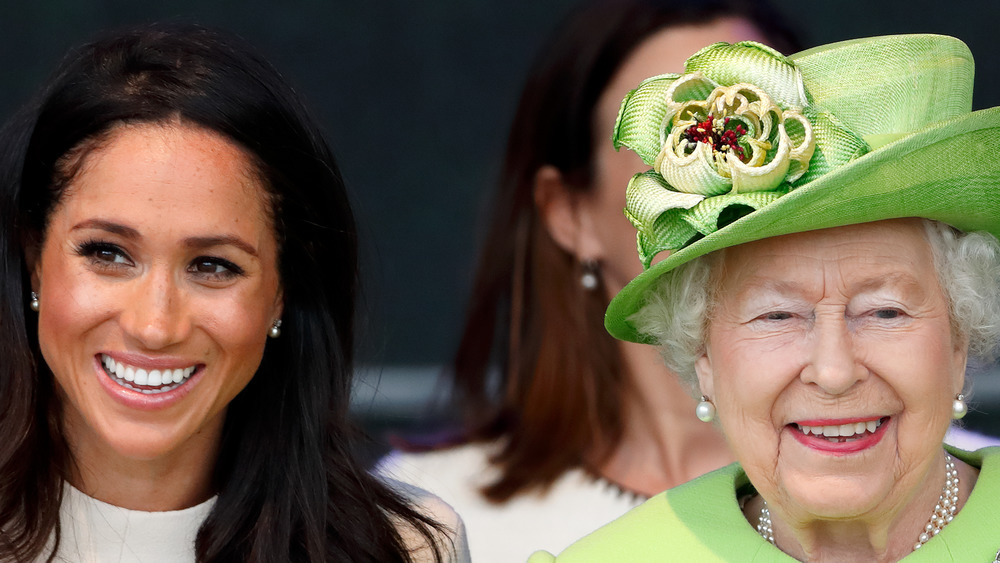 Meghan Markle smiles with the Queen