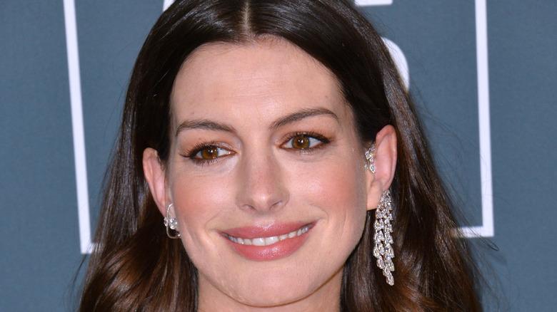 Anne Hathaway smiling, wearing earrings