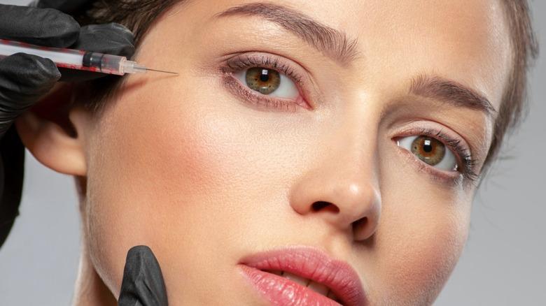 Woman's face alongside needle for under eye filler injection