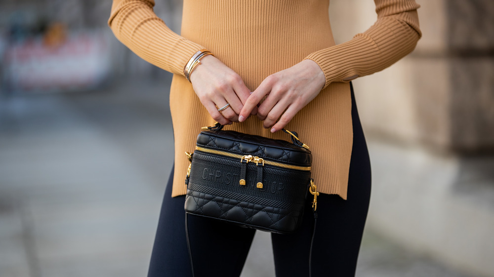 woman in leggings holding a purse