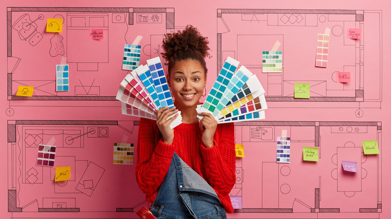 girl holding up color swatches trying to decide what to paint where