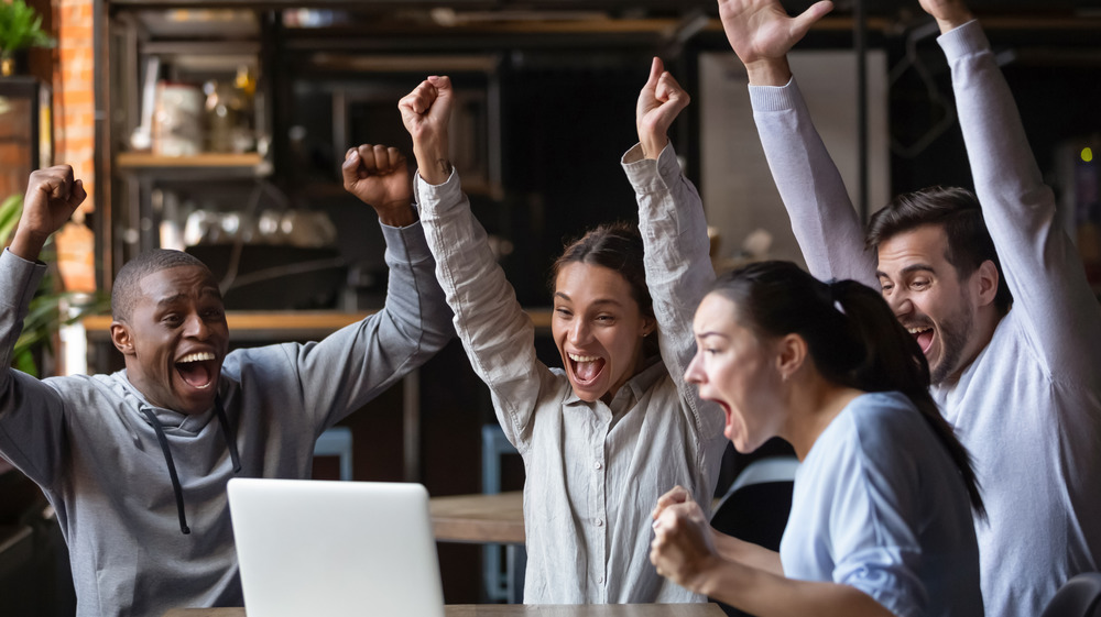 Friends cheering at a computer