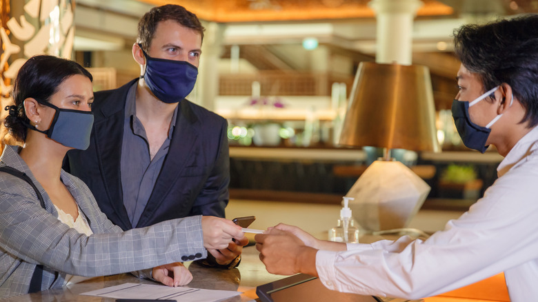 Couple in masks checking into hotel