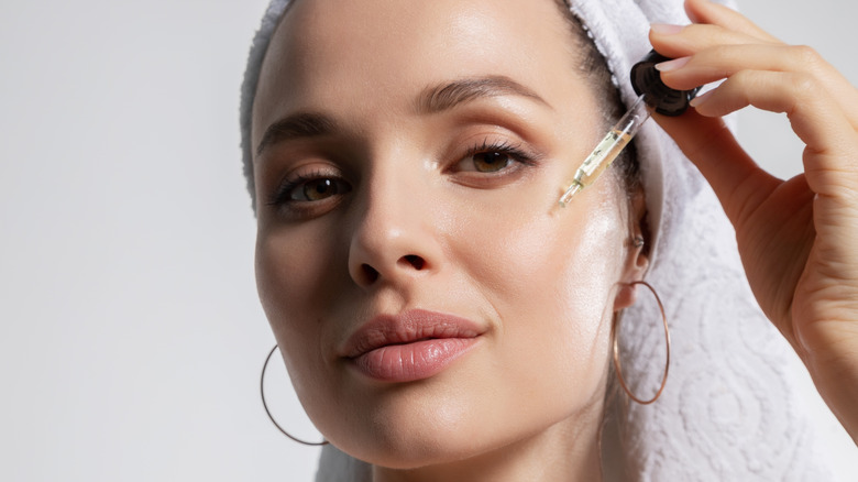 Young woman applying a peptide serum