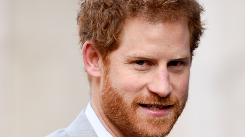 Prince Harry smiling in a gray suit