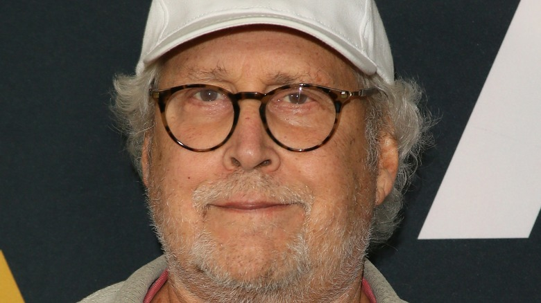 Chevy Chase in glasses and a ball cap
