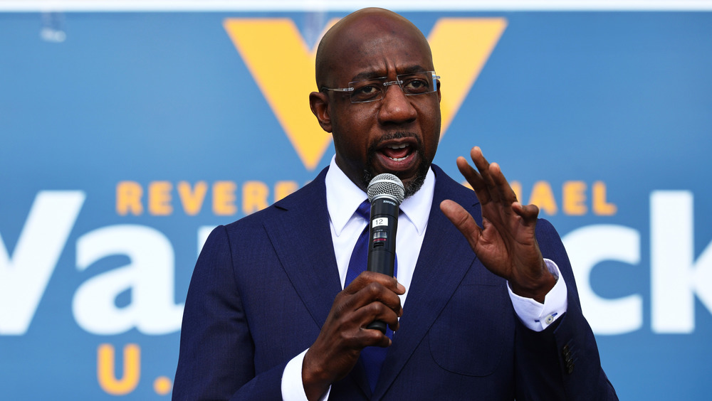Raphael Warnock speaking at rally in blue suit