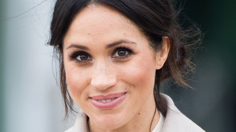 Meghan Markle with her hair pulled into a low bun smiling for a picture