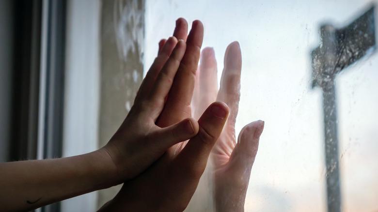 Hands touching through glass