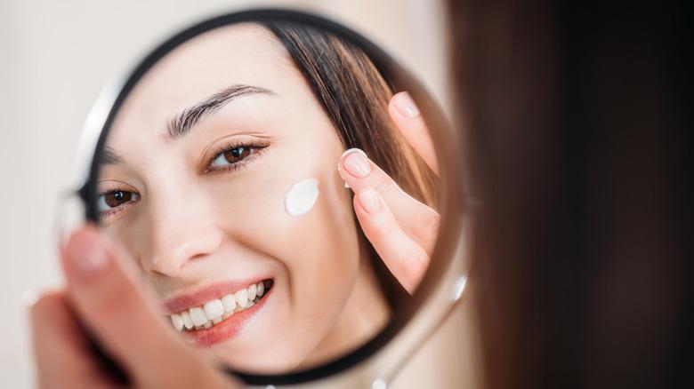 Woman rubbing cream on her skin